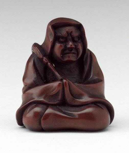 An image of Netsuke in the form of a seated Daruma, holding a fly whisk by