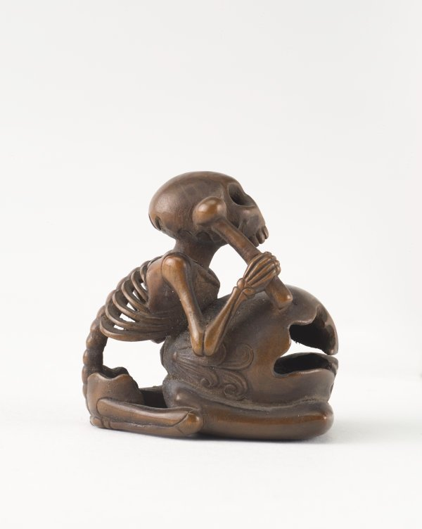 An image of Netsuke in the form of a seated skeleton hitting a 'wooden fish' bell ('mokugyo')