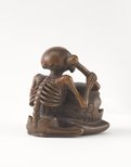 Alternate image of Netsuke in the form of a seated skeleton hitting a 'wooden fish' bell ('mokugyo') by