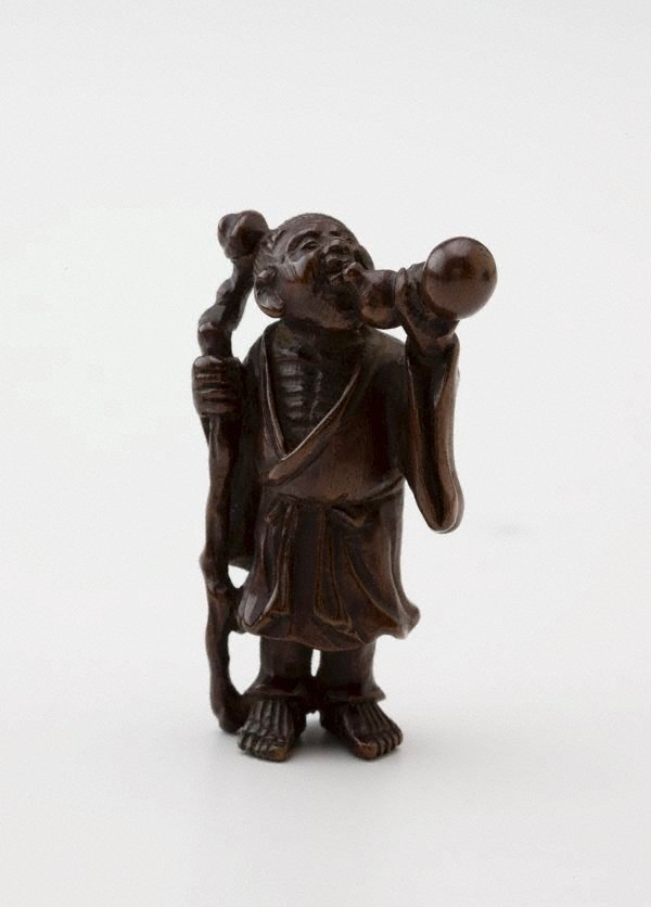 An image of Netsuke in the form of Chôkarô 'sennin' with a staff, drinking from a gourd