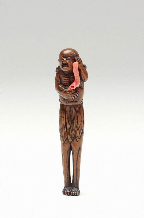 An image of Netsuke in the form of an old South Sea Islander holding red coral
