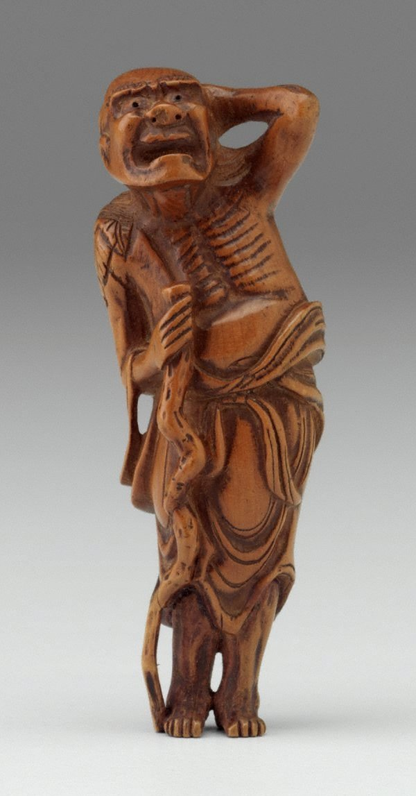 An image of Netsuke in the form of a 'sennin' (mountain recluse) holding his hair and a staff