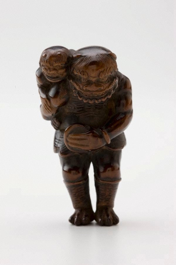 An image of Netsuke in the form of 'oni' carrying a child on his back, and a bowl in front