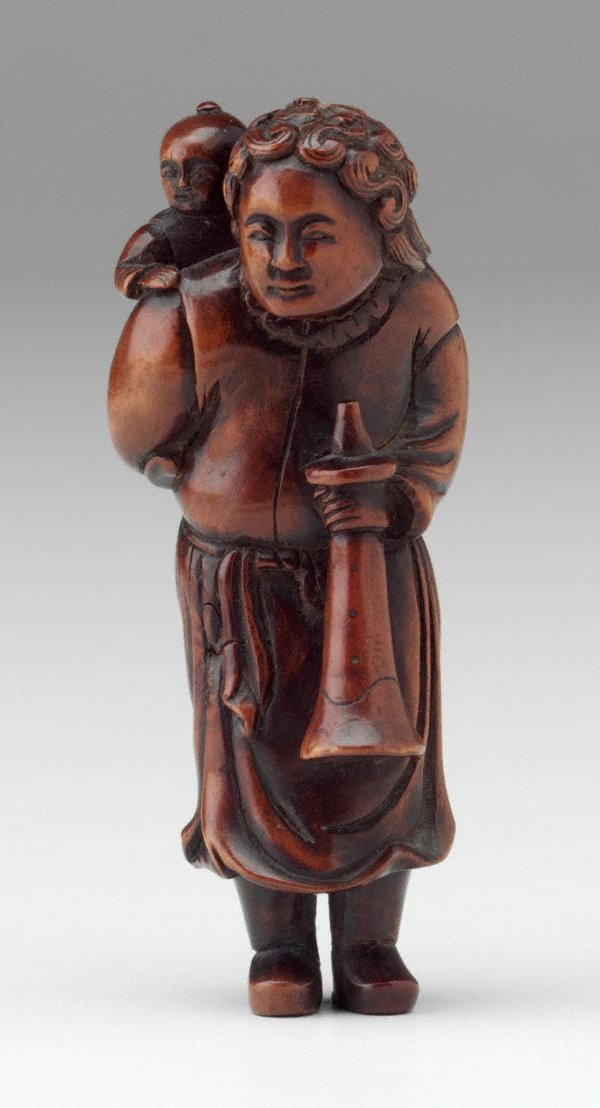 An image of Netsuke in the form of a curly-haired Dutchman carrying a child on his back, holding a horn