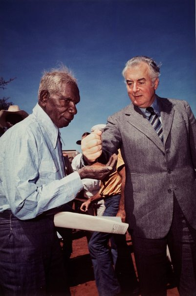 An image of Prime Minister Gough Whitlam pours soil into the hands of traditional land owner Vincent Lingiari, Northern Territory by Mervyn Bishop
