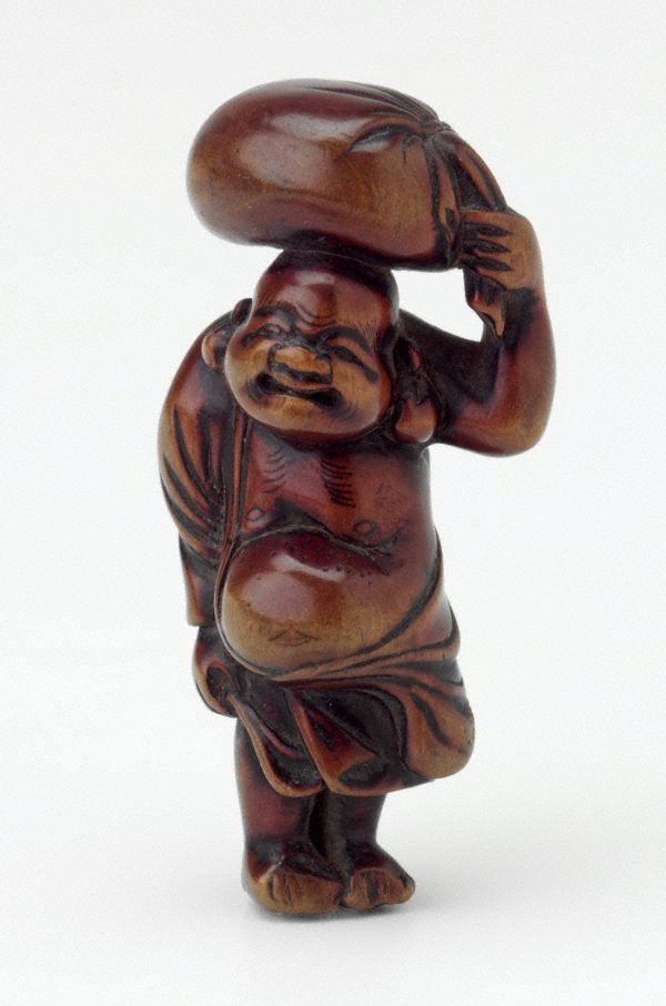 An image of Netsuke in the form of Daikoku carrying a sack on his head