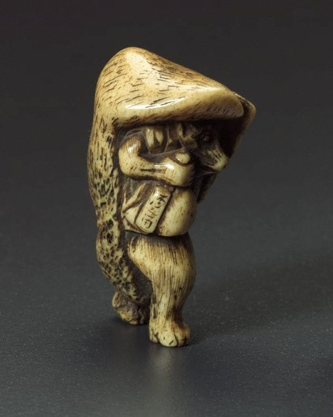 An image of Netsuke in the form of a tanuki (raccoon dog) carrying a 'sake' bottle by