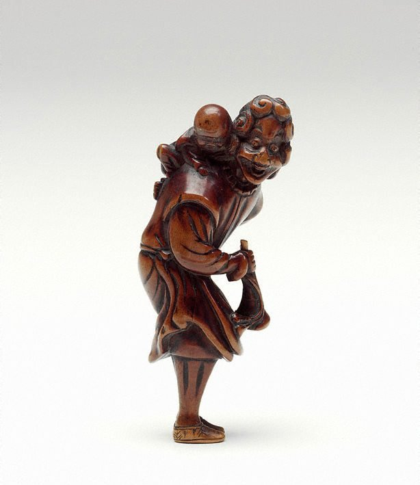 An image of Netsuke in the form of a foreigner with a coat, carrying a child and a horn