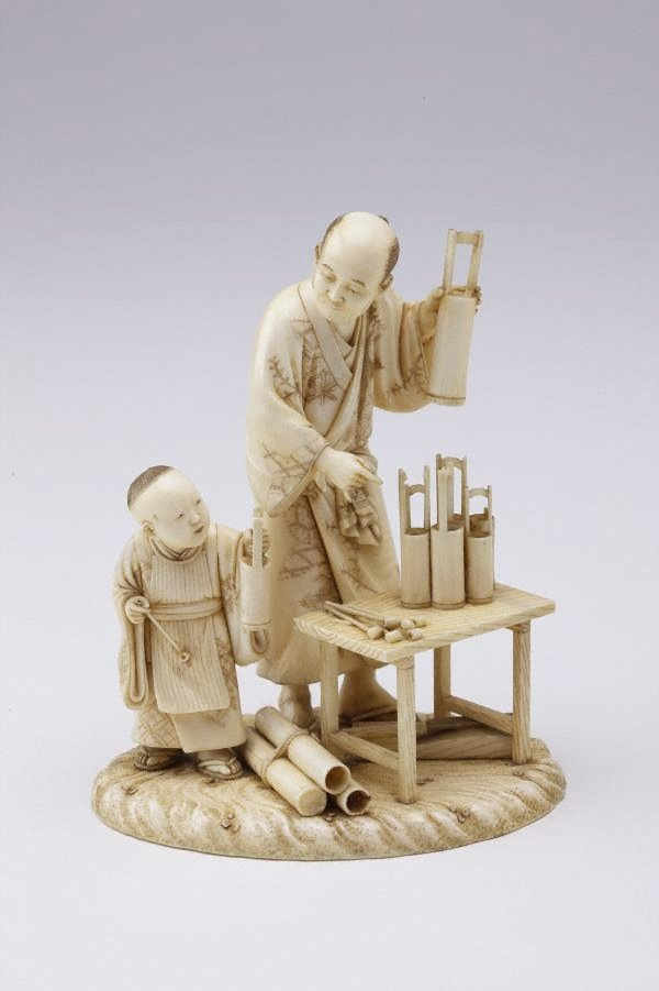 An image of Group of bamboo vase maker and boy (okimono)
