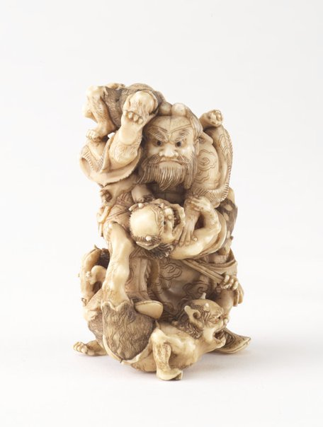 An image of Netsuke in the form of a man fighting demons by Tomomasa