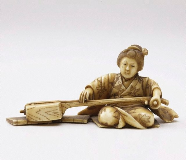 An image of Figure of a seated woman playing shamisen (okimono)
