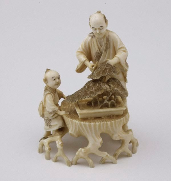 An image of Man trimming bonsai tree and child seated nearby watching (okimono)