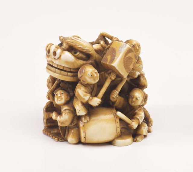 An image of Netsuke in the form of a festival group with a mask, drums and lanterns