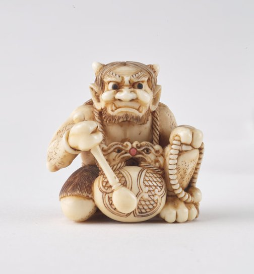 An image of Netsuke in the form of a demon chanting Buddhist sutra by