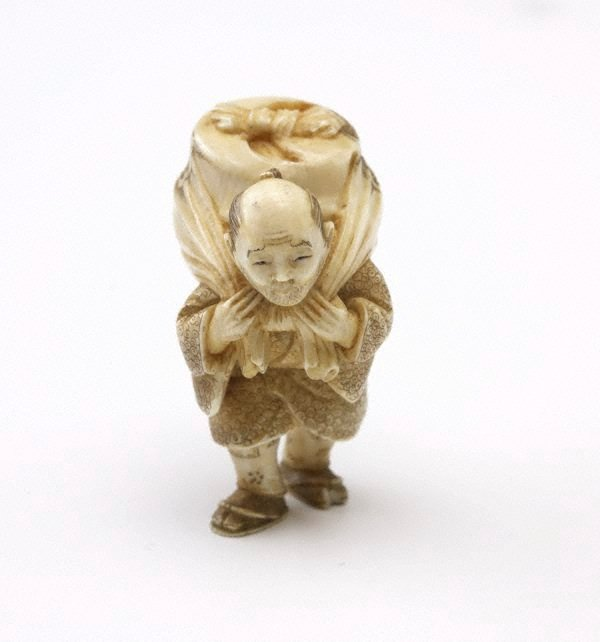 An image of Netsuke in the form of a man carrying a bundle on his back