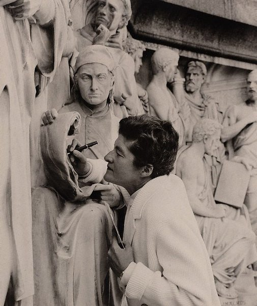 An image of Nancy Spain at the Albert Memorial, London, annotating Voltaire's notebook by Lewis Morley
