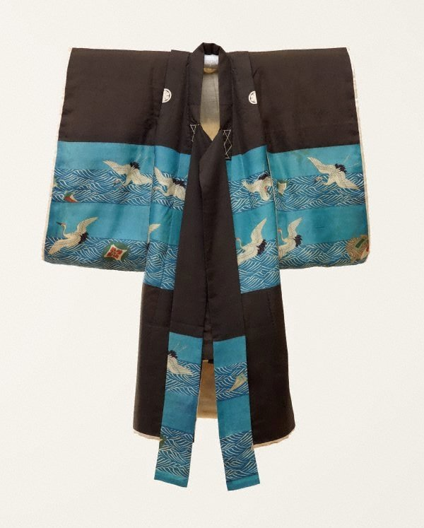 An image of Kimono for first presentation of baby at Shinto shrine (Miyamairi kimono) with design of cranes over waves and auspicious instruments