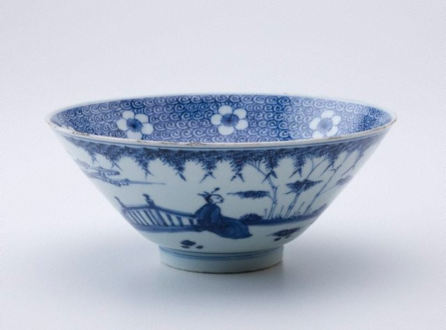 An image of Bowl with bands of white prunus blossoms on a blue sea scroll background; exterior decorated with figures in a landscape