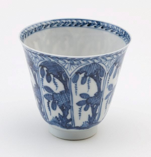 An image of Cup decorated with leaves and trees within arched panels