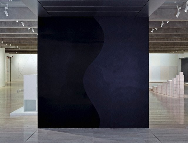 An image of Wall drawing #871: A black square divided vertically by a wavy line. Left: glossy; right: flat