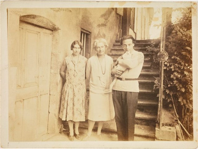 An image of Anne Dangar in between Monsieur and Madame Pouyaud and Poulette the cat at the door of her house in Moly-Sabata, France