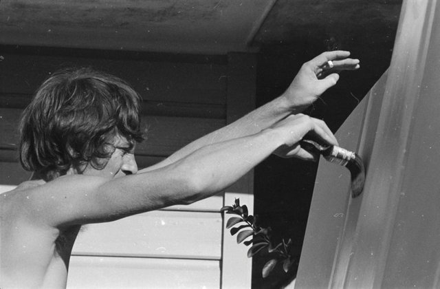 An image of Peter Powditch painting a mural for the Sydney Airport