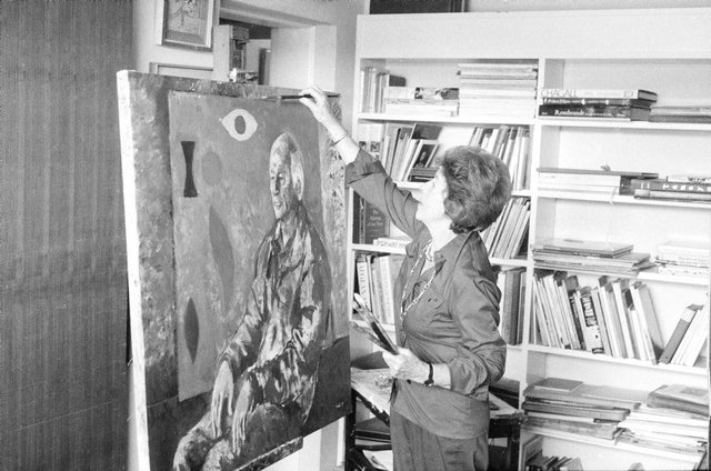 An image of Judy Cassab in her studio, painting a portrait of artist John Coburn