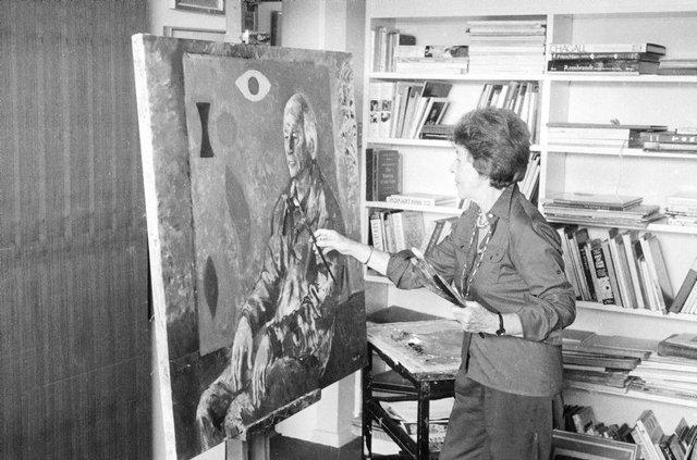 An image of Judy Cassab in her studio, painting a portrait of artist John Coburn