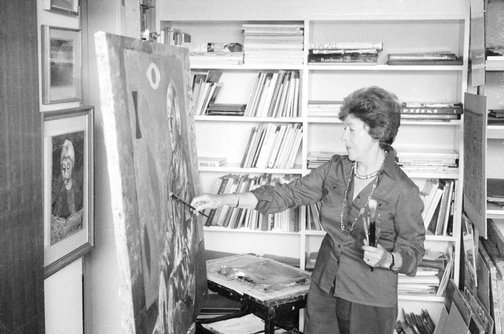 An image of Judy Cassab in her studio, painting a portrait of artist John Coburn by Robert Walker