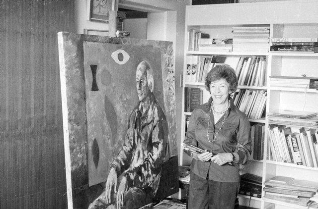 An image of Judy Cassab in her studio with her portrait of artist John Coburn