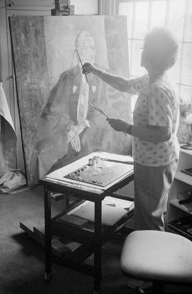 An image of Judy Cassab in her studio painting a portrait of the Dean of Wesley College, University of Sydney by Robert Walker