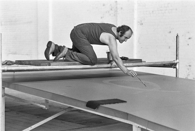 An image of John Olsen in his wool store studio working on the 'Salute to Five Bells' mural for the Sydney Opera House
