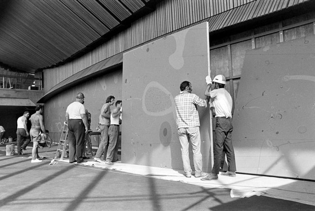 An image of John Olsen's mural panels for 'Salute to Five Bells' being lifted into position in the northern foyer of the main concert hall, Sydney Opera House