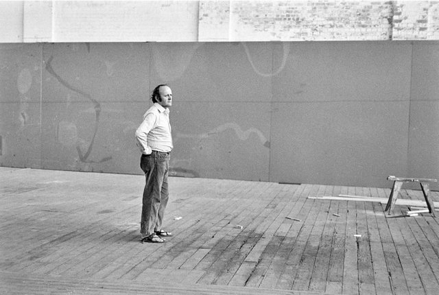 An image of John Olsen in his wool store studio contemplating his 'Salute to Five Bells' mural for the Sydney Opera House