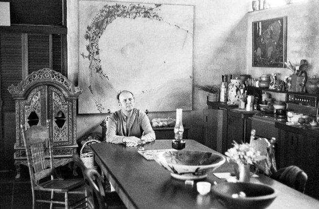 An image of John Olsen in his dining room at Dural with his painting 'Lake Hindmarsh' 1970 in the background