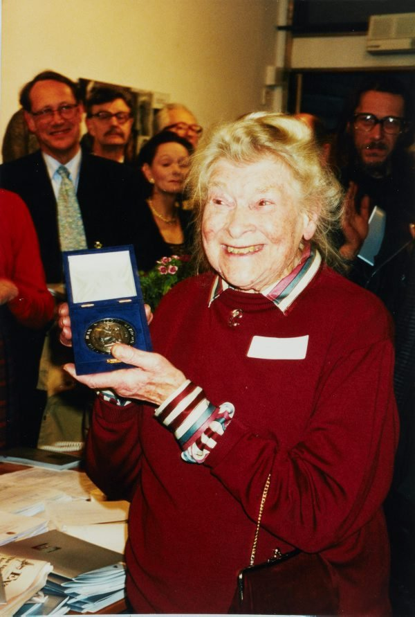 An image of Barbara Tribe holding the Jean Masson Davidson Medal, awarded by the Society of Portrait Sculptors
