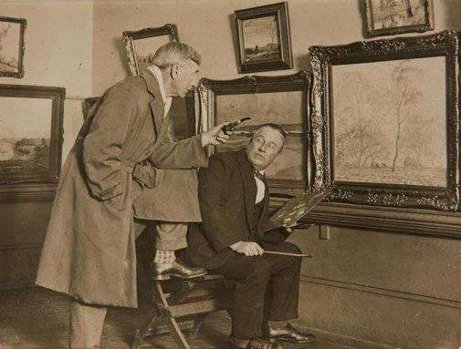 An image of Charles Bryant retouching his painting 'Frosty Morning' before the opening of the 1929 annual exhibition of the Royal Art Society, with Sydney Long making a comment on the work by William Rubery Bennett