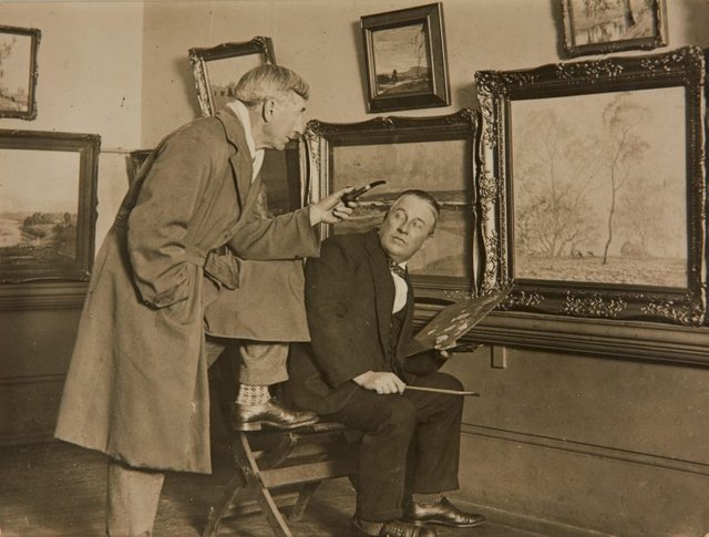An image of Charles Bryant retouching his painting 'Frosty Morning' before the opening of the 1929 annual exhibition of the Royal Art Society, with Sydney Long making a comment on the work