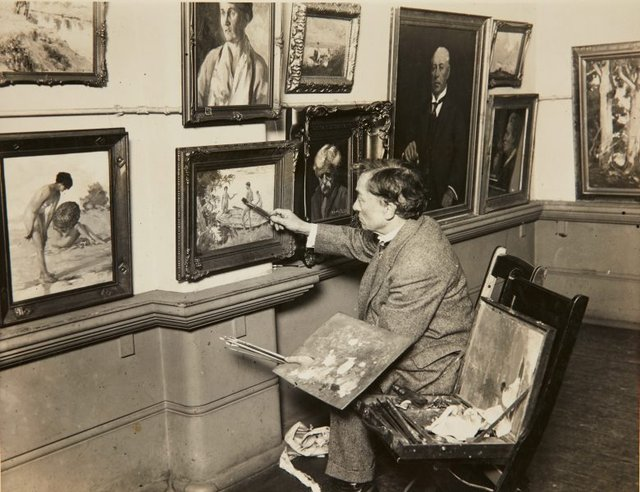 An image of J. S. Watkins retouching his painting 'The holiday' before the opening of the 1929 Royal Art Society Annual Exhibition