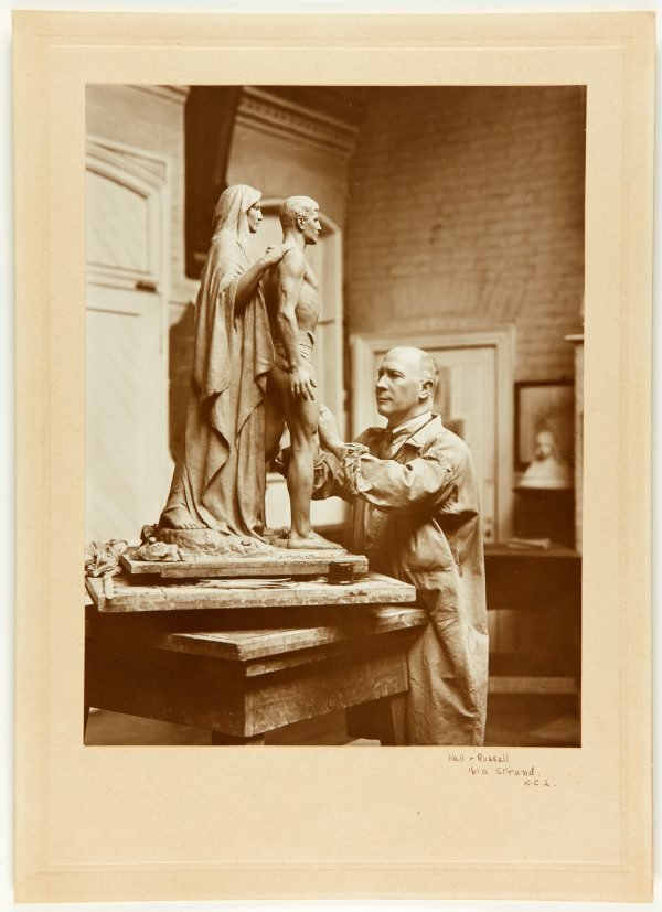 An image of Bertram Mackennal working on the plaster cast of the figures for his Blackburn War Memorial