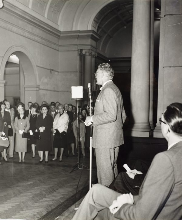 An image of Hal Missingham speaking at the installation of the Tutini (Pukumani grave posts) at the Art Gallery of New South Wales
