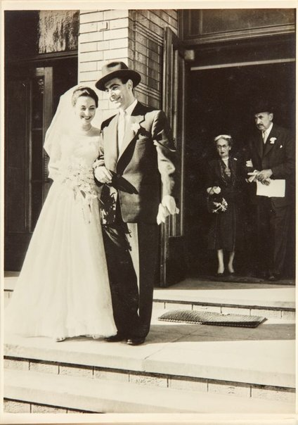 An image of Robert Klippel and Nina Mermey on their wedding day with Klippel's parents in the background by Unknown photographer