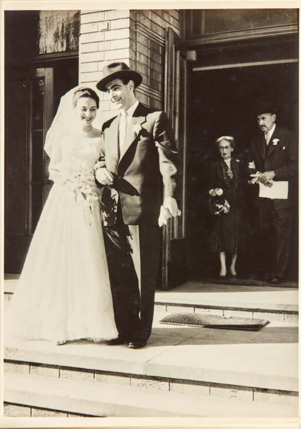 An image of Robert Klippel and Nina Mermey on their wedding day with Klippel's parents in the background