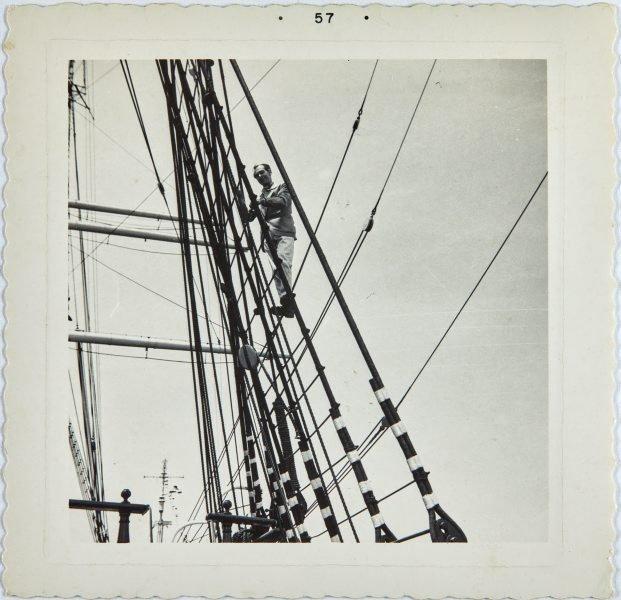 An image of Robert Klippel climbing ropes on a sail boat  in San Francisco