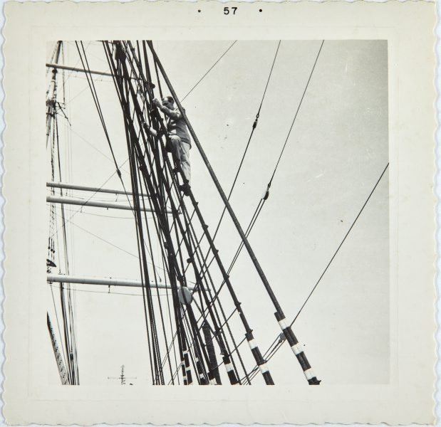 An image of Robert Klippel climbing ropes aboard a sail boat in San Francisco