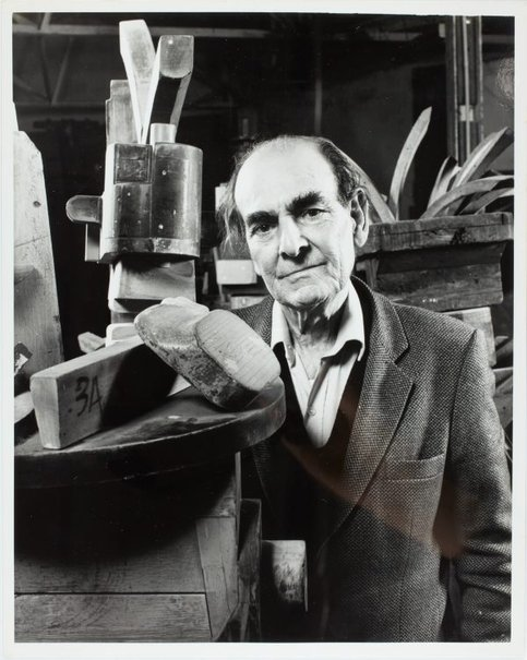 An image of Robert Klippel with wooden pattern-part sculptures by