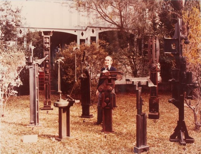 An image of Robert Klippel with bronzes in the garden at Birchgrove