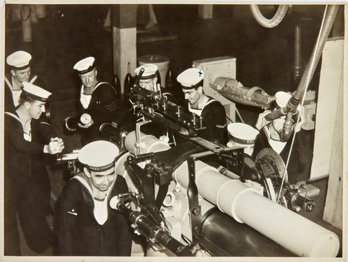 An image of Robert Klippel and fellow naval officers with naval artillery by