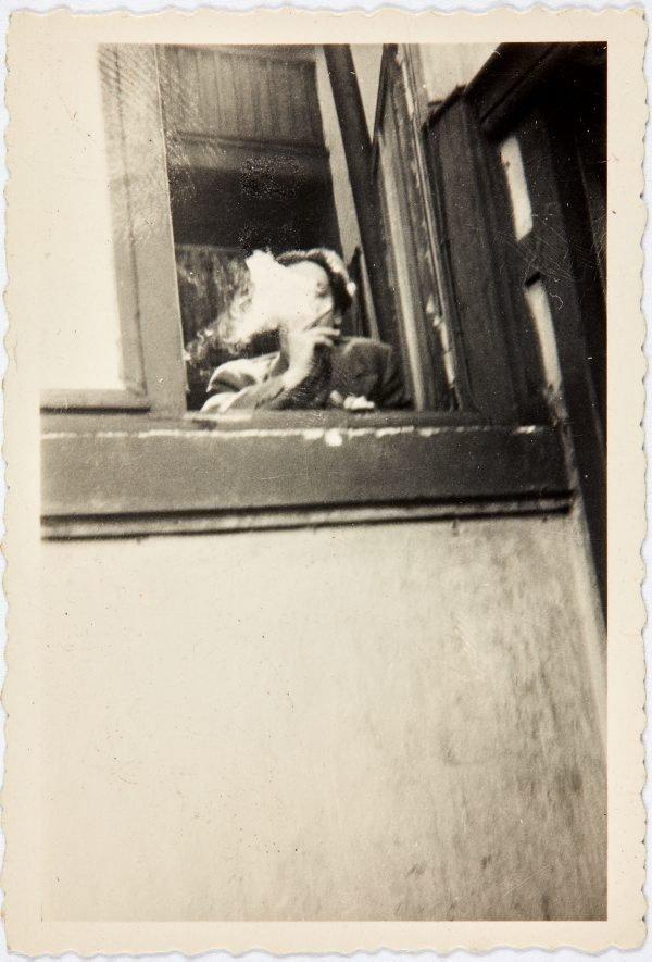 An image of Nina Mermey smoking at a window