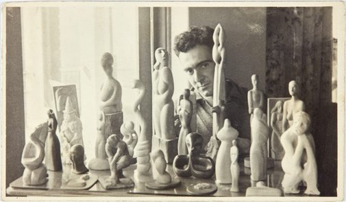 An image of Robert Klippel with a group of his early carvings by